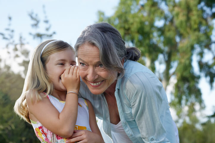 Closeup of a young girl whispering in grandmother's ear outdoors